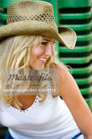 Portrait de jeune blonde cowgirl au chapeau de cow-boy, assis sur le tracteur à l'extérieur