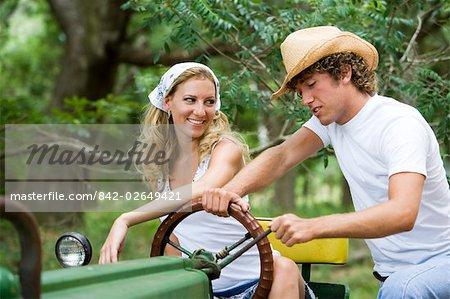 Jeunes cow-boys et cow-girl, siégeant à l'extérieur du tracteur