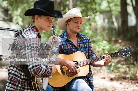 Deux jeunes cow-boys, jouant de la guitare et au banjo près de vieux camion à l'extérieur