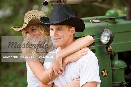Jeunes cow-boys et cow-girl, porter un chapeau de cowboy siégeant à l'extérieur du tracteur
