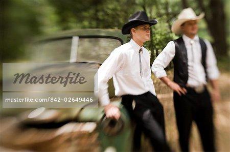 Deux jeunes cow-boys debout près de vintage camion à l'extérieur