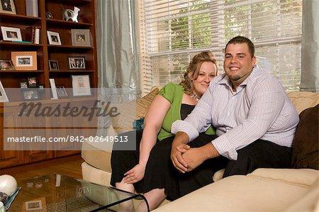Portrait d'un excès de poids caucasien couple assis sur le canapé dans le salon