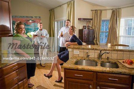 Portrait de quatre amis de race blanche assis avec boissons dans la cuisine