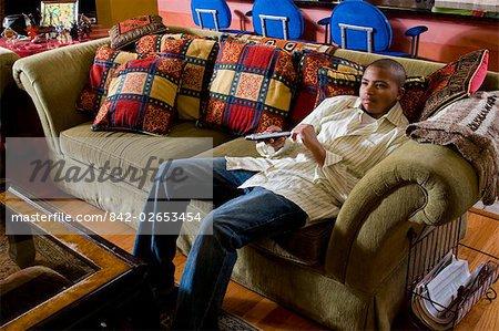 African American Teenager sitzen auf der Couch vor dem Fernseher mit Fernbedienung