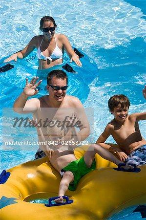 Vue surélevée de la famille de s'amuser au parc aquatique avec enfants assis sur chambres à air
