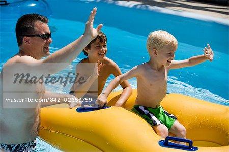 Famille et fils flottant sur chambre à air à un parc aquatique