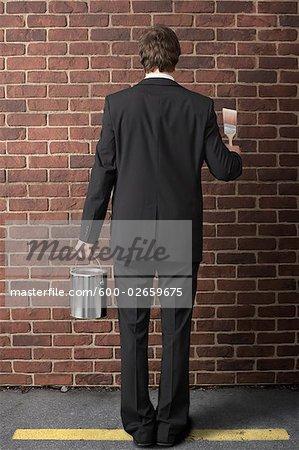 Homme d'affaires peinture sur le mur de brique