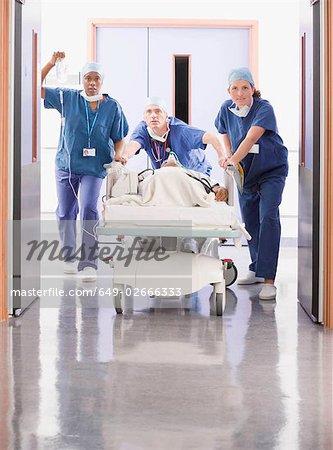 Trois médecins poussant un patient dans son lit