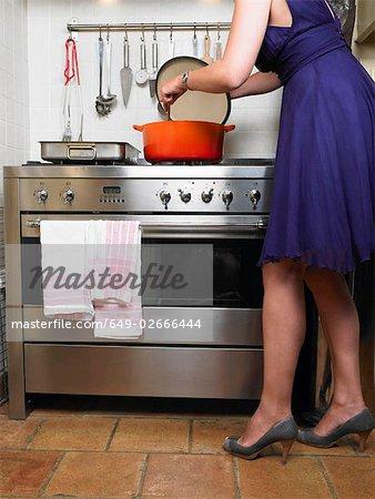 Femme en robe du soir de cuisine