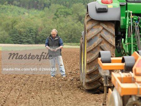 Agriculteur examinant sol sur terrain