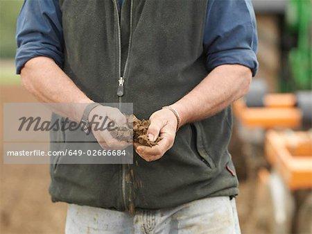 Mains de l'agriculteur tenant du sol