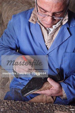 Italian Shoemaker Spreading Glue on Sole of Boot
