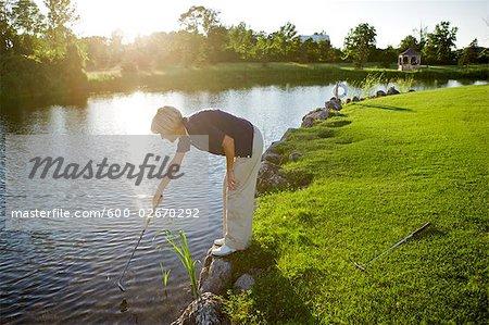 Frau sucht Golfball in Wasser, Burlington, Ontario, Kanada