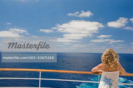 Femme regardant l'océan de la poupe du navire de croisière