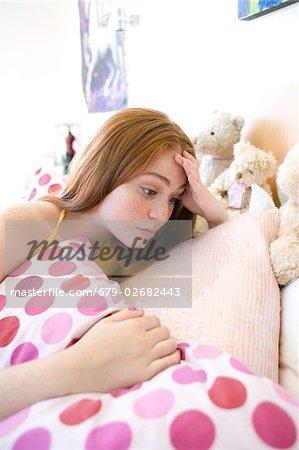 Depressed teenage girl lying on her bed.