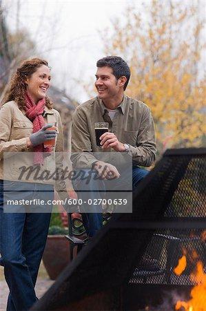 Couple, boire de la bière par une cheminée extérieure, Bend, Oregon, Etats-Unis