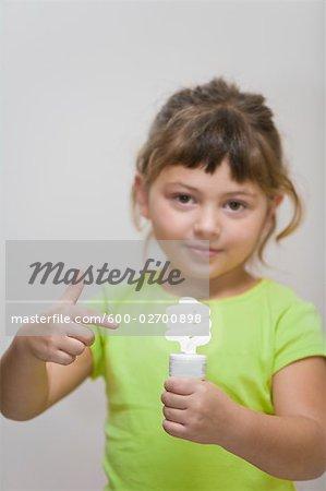 Little Girl Holding Energy Efficient Lightbulb