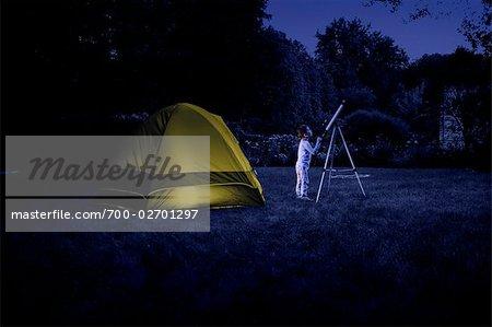 Boy Camping in Backyard, Looking at Night Sky Through a Telescope