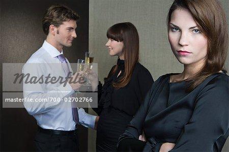 Femme à la recherche en colère comme un Couple dans l'arrière-plan porter un Toast