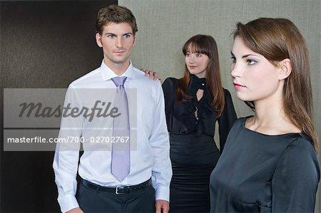 Mann, die Frau zu betrachten, während eine andere Frau seine Schulter packt