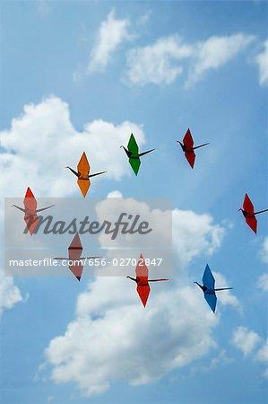multiple paper cranes against sky backdrop
