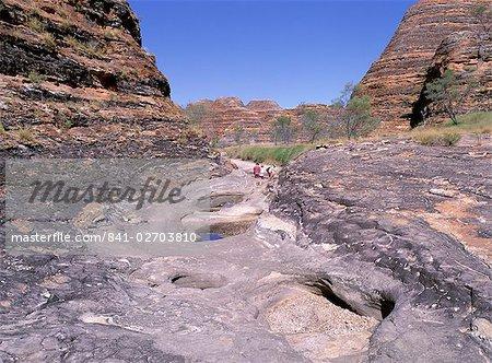 Touristes traversent les roches inondation décapée, au-delà des formations typiques, Parc National de Purnululu, Site du patrimoine mondial de l'UNESCO, Bungle Bungle, Kimberley, Australie-occidentale, Australie, Pacifique