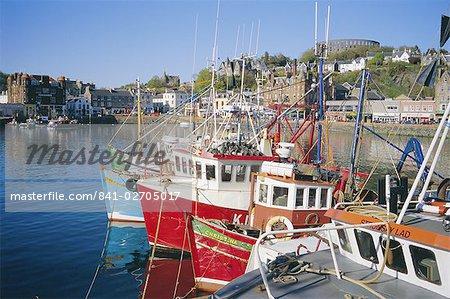 Bateaux de pêche et front de mer avec tour de McCaig sur la colline, Argyll, Écosse, Royaume-Uni, Europe