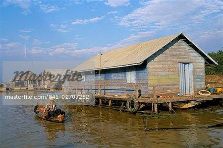 Homme en canoë, en passant d'une maison flottante de village de pêche de Chong Kneas, lac Tonlé Sap, près de Siem Reap, Cambodge, Indochine, Asie du sud-est, Asie