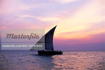 Boutre dans la silhouette de l'océan Indien au coucher du soleil, large de Stone Town, Zanzibar, Tanzanie, Afrique de l'est, Afrique