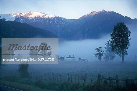 Farm in mist below Fox Glacier, Westland, west coast, South Island, New Zealand, Pacific
