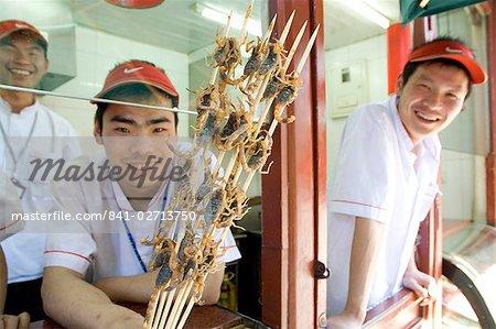 Manger une collation des brochettes de scorpion dans un hutong près de Wang Fu Jing road, où les sauterelles, hippocampe, serpents, larve et étoile de mer également servis, Beijing, Chine, Asie
