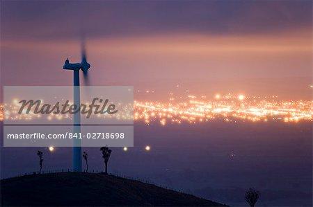 Te Apiti éolien à l'aube, sur les gammes Ruahine inférieures, avec les lumières de Palmerston North au-delà, Manawatu, North Island, Nouvelle-Zélande, Pacifique