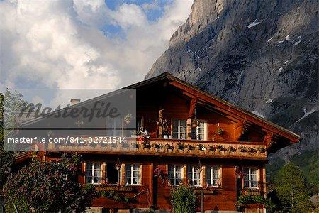 Lady arrosant les fleurs sur le chalet, Grindelwald, Berne, Suisse, Europe