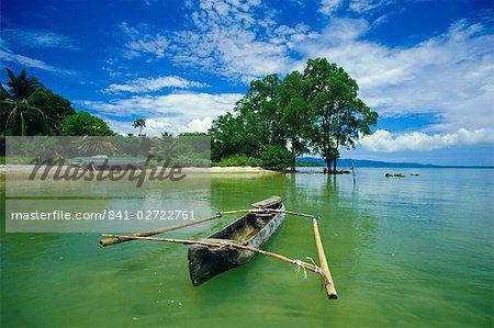 Outrigger canoe et plage, réserve de Ujong Kulon, Handeuleum de l'île, Ouest Java, Indonésie