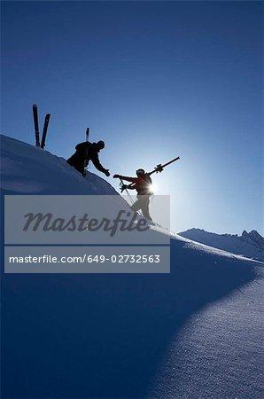 Skifahrer, die einander helfen, am Berg