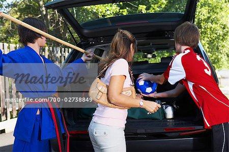 Garçons en karaté et football uniformes aident le Pack Mom la voiture