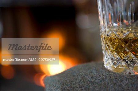 Gros plan d'un verre de whisky devant une cheminée