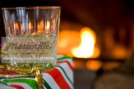 Gros plan d'un verre de whisky dans une boîte cadeau devant un feu de bois