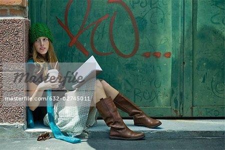Jeune femme assise sur le sol avec le livre et la boisson, à la recherche de suite