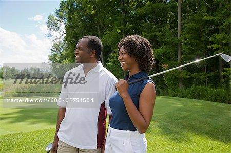 Paar halten Golfclubs