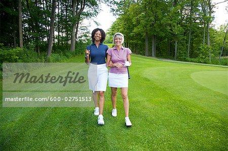 Frauen, die zu Fuß am Golfplatz