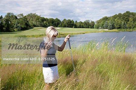 Golfspieler, die Suche nach Ball in hohem Gras