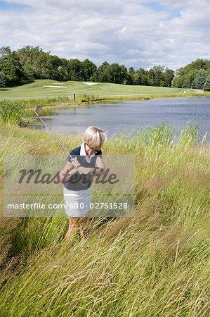 Seitenansicht einer Frau Golfen in hohem Gras