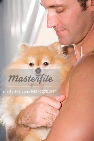 Chien de Poméranie holding homme torse nu musculaire dans les bras