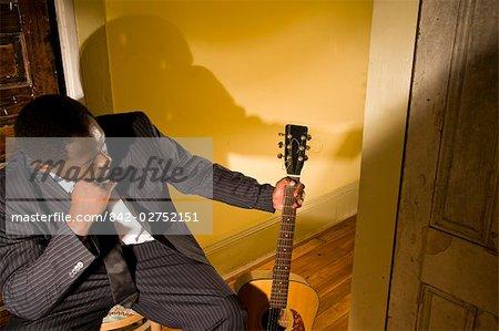 Portrait d'un musicien afro-américain dans le couloir avec guitare