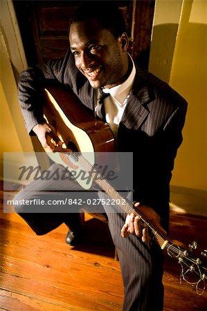 Portrait du musicien afro-américain, jouer de la guitare dans le couloir de la maison