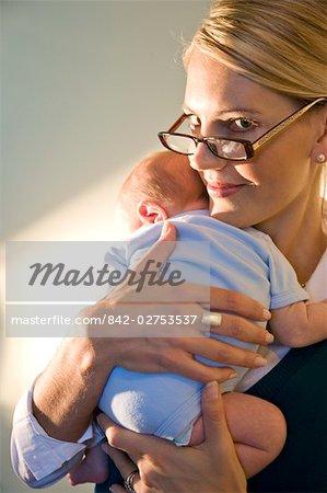 Portrait de bébé holding jeune femme d'affaires dans les bras