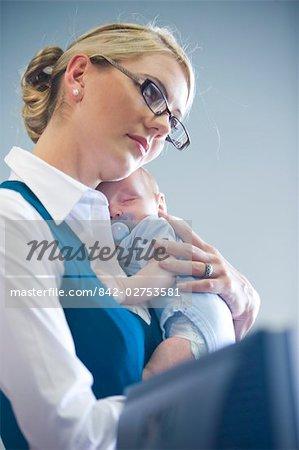 Portrait de jeune femme d'affaires tenue bébé endormi au travail
