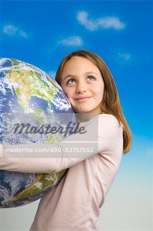 Petite fille tenant un modèle de terre vu de l'espace extra-atmosphérique