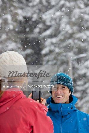 Femme prenant la photo de l'homme avec le téléphone appareil photo à l'extérieur en hiver, Whistler, Colombie-Britannique, Canada